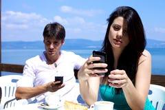 Ami et amie texting pendant le déjeuner Image libre de droits