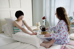 Ami féminin apportant le petit déjeuner pour son ami Image stock