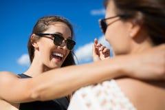 Ami féminin de embrassement de jeune femme heureuse lui disant quelque chose Photos stock
