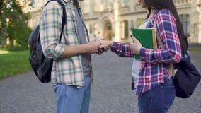 Ami frottant et embrassant la main de l'amie, couple affectueux des étudiants banque de vidéos