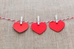 Ami il cavo naturale dei cuori del biglietto di S. Valentino e l'attaccatura bianca delle clip Fotografia Stock