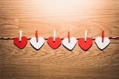 Ami il cavo naturale dei cuori del biglietto di S. Valentino e l'attaccatura rossa delle clip Fotografia Stock Libera da Diritti