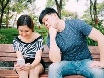 Ami jaloux jetant un coup d'oeil et remarquant son téléphone portable d'amie Images libres de droits