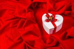Ami la carta con cuore su un tessuto rosso Immagine Stock