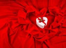 Ami la carta con cuore su un tessuto rosso Immagini Stock