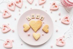 AMI la parola ed il cuore ha modellato i biscotti su un piatto rosa fotografia stock
