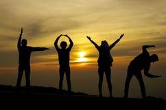 Ami la siluetta da quattro genti sul fondo dell'alba Fotografia Stock