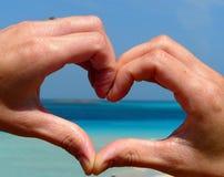 Ami la siluetta della mano di forma sopra la spiaggia di Pelosa alla Sardegna, Italia Immagine Stock