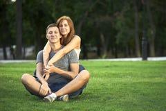 Ami le coppie che si siedono sull'erba nel parco immagini stock libere da diritti