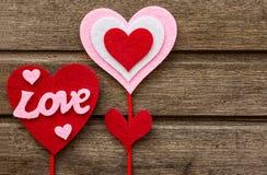 Ami le decorazioni sul fondo di legno di struttura, biglietti di S. Valentino dei cuori Immagine Stock