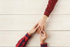 Ami mettant l'anneau sur le doigt d'amie, vue supérieure Photographie stock libre de droits