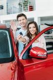 Ami ondulant une main, amie montrant la clé de la nouvelle voiture Image libre de droits