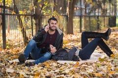 Ami parlant au téléphone tout en appréciant Autumn Park Photographie stock libre de droits
