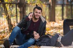 Ami parlant au téléphone tout en appréciant Autumn Park Image libre de droits