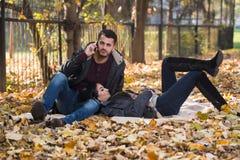 Ami parlant au téléphone tout en appréciant Autumn Park Images libres de droits
