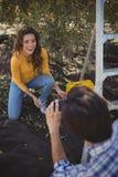 Ami photographiant l'amie de sourire à la ferme olive Images stock