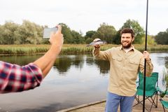Ami photographiant le p?cheur avec des poissons au lac photo stock