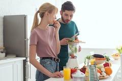 ami préparant le jus de légumes avec le presse-fruits à la cuisine photographie stock libre de droits