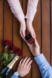 Ami proposant l'amie et tenant l'anneau de mariage Photo libre de droits