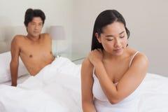 Ami regardant l'amie s'asseyant sur l'extrémité du lit Photo stock
