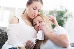 Ami soulageant son ami pleurant à la maison Images libres de droits