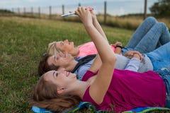 Ami trois détendant sur la couverture colorée en parc été Image stock