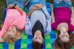 Ami trois détendant sur la couverture colorée en parc été Images libres de droits