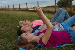 Ami trois détendant sur la couverture colorée en parc été Photographie stock
