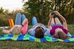 Ami trois détendant sur la couverture colorée en parc été Images stock