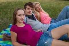 Ami trois détendant sur la couverture colorée en parc été Image libre de droits