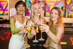 Ami trois de sourire grillant le verre de champagne Photo libre de droits