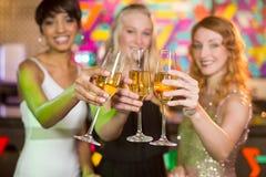 Ami trois de sourire grillant le verre de champagne Photo stock