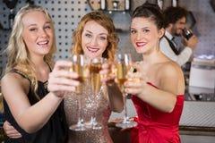 Ami trois de sourire montrant le verre de champagne Photo stock