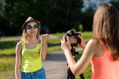 Amica dell'adolescente di due ragazze Riposo di sorrisi Mostra il suo pugno e ride Emozioni di potere Vlog e blog record Immagine Stock