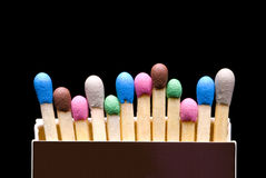 Amicable family. Multi-coloured matches in a box (a black background stock images