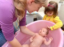 The amicable family bathes the baby in a pink tray Royalty Free Stock Photo