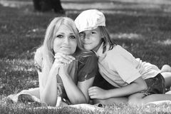 Amicable family on nice grassy lawn monochrome image. Family harmony. Beautiful mother with her son in fashionable stylish cap lying on a green grassy lawn in a Stock Images