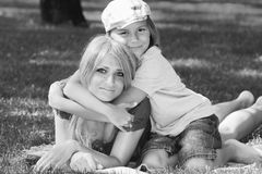 Amicable family on nice grassy lawn monochrome image. Family harmony. Beautiful mother with her son in fashionable stylish cap lying on a green grassy lawn in a stock photography