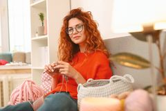Amicable girl with ginger hair sitting near big window. Amicable girl. Amicable beautiful girl with long wavy ginger hair sitting near big window while knitting stock image