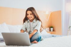 Amicable young girl smiling while watching cartoon. Watching cartoon. Amicable young girl smiling while feeling very funny watching comedian cartoon stock photography
