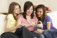 Amiche adolescenti che leggono telefono mobile nel paese Immagine Stock