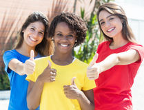 Amiche afroamericane e caucasiche in camice variopinte che mostrano i pollici Immagine Stock