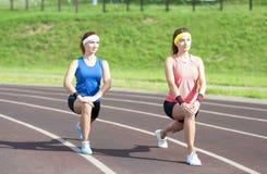 Amiche caucasiche che hanno allungamento degli esercizi sulla sede di sport all'aperto Fotografia Stock