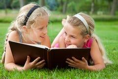 Amiche che leggono un libro all'aperto Immagini Stock Libere da Diritti