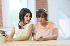 Amiche che per mezzo degli smartphones a casa Fotografia Stock Libera da Diritti