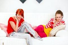 Amiche che si siedono sul sofà e che comunicano sui mobiles fotografie stock
