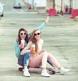Amiche dei pantaloni a vita bassa che prendono un selfie in città urbana Immagini Stock Libere da Diritti