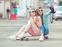 Amiche dei pantaloni a vita bassa che prendono un selfie in città urbana Fotografia Stock Libera da Diritti