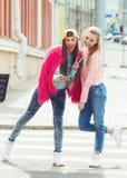 Amiche dei pantaloni a vita bassa che prendono un selfie in città urbana Fotografia Stock