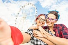 Amiche delle giovani donne che prendono selfie alla ruota di ferris su pubblico Fotografie Stock Libere da Diritti